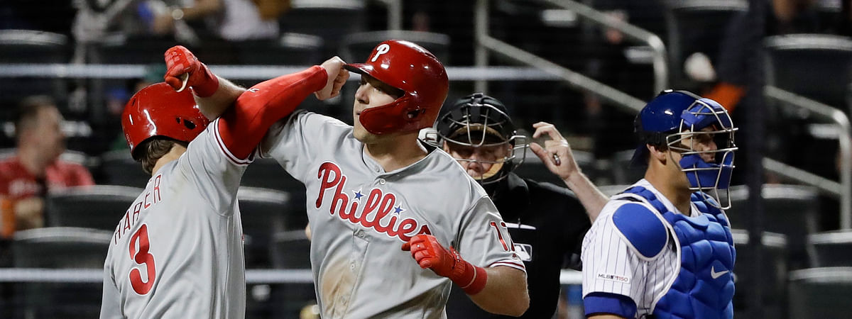 Mets catcher Wilson Ramos looks away as Phillies' Bryce Harper, left, celebrates with Rhys Hoskins, center, after Hoskins hit a two-run home run in the ninth inning, Wednesday. (AP Photo/Frank Franklin II)