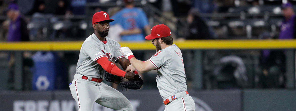 Philadelphia Phillies right fielder Bryce Harper, right, dunks his glove into the arms of Phillies center fielder Andrew McCutchen after beating the Colorado Rockies on April 20, 2019.