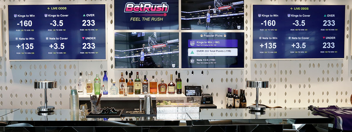 In this March 19, 2019, photo video screens display the types of bets that can be placed at the Golden 1 Center's Skyloft Predictive Gaming Lounge, in Sacramento, Calif. In some states, including California, allowing sports betting would probably require a constitutional amendment.  (AP Photo/Rich Pedroncelli)