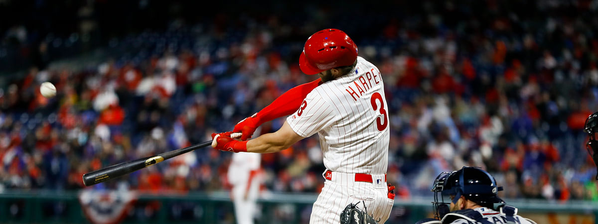 Philadelphia Phillies' Bryce Harper, left, hits a homerun off Atlanta Braves relief pitcher Shane Carle during the seventh inning on March 31, 2019.