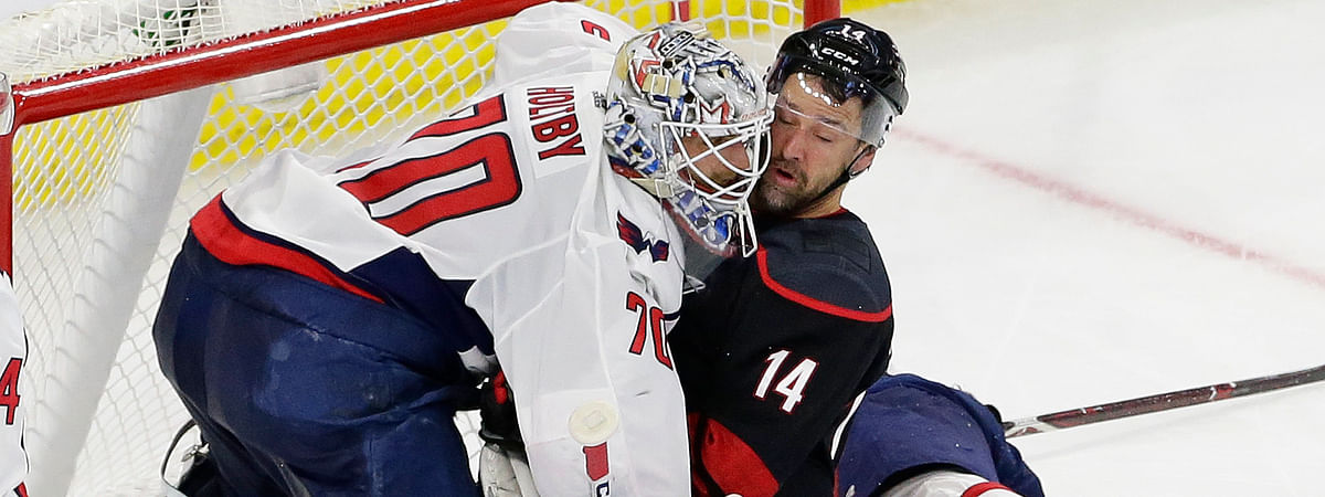 Carolina Hurricanes' Justin Williams (14) collides with Washington Capitals goalie Braden Holtby (70) during the second period of Game 6 of an NHL hockey first-round playoff series on April 22, 2019.