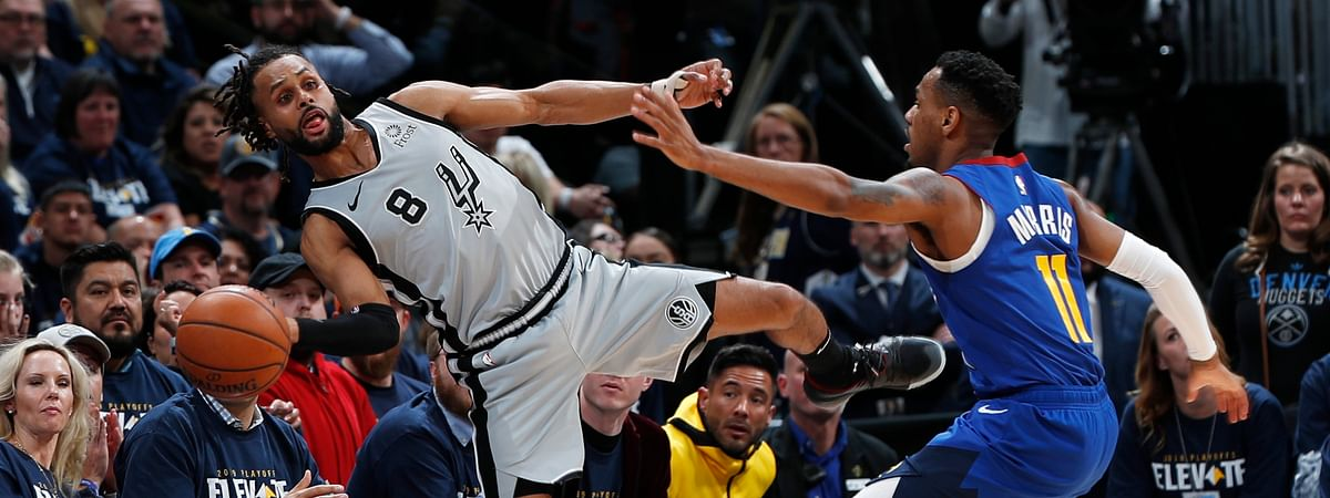 San Antonio Spurs guard Patty Mills, left, reaches out to save a ball from going out of bounds as Denver Nuggets guard Monte Morris defends in the second half of Game 1 of an NBA first-round basketball playoff series, Saturday, April 13, 2019, in Denver. The Spurs won 101-96. (AP Photo/David Zalubowski)