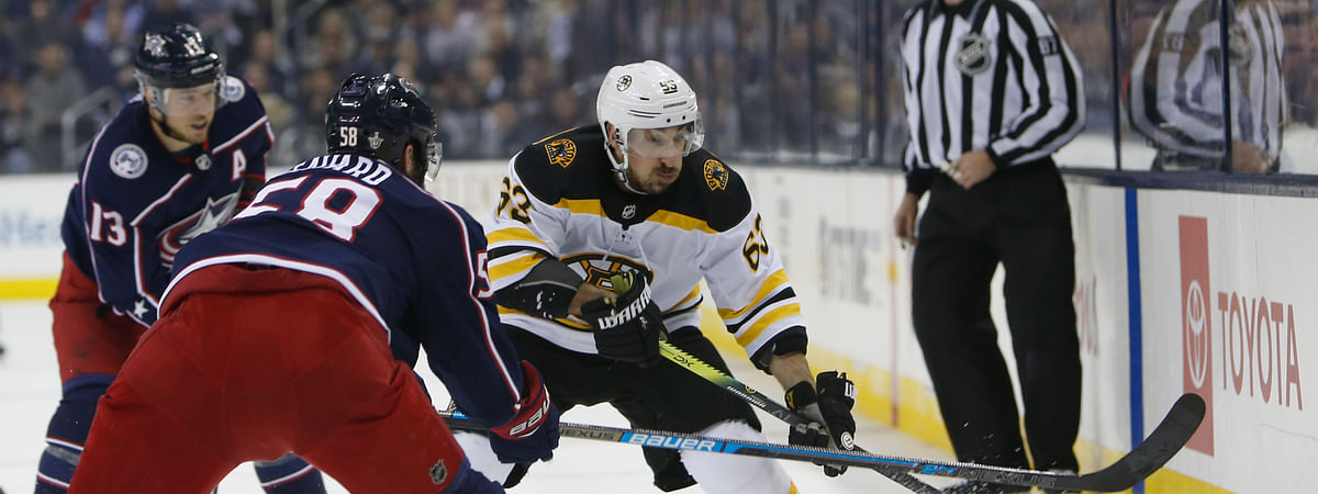 Boston Bruins' Brad Marchand, right, carries the puck across the blue line against Columbus Blue Jackets' David Savard during the first period of Game 3 of the NHL hockey second-round playoff series on April 30, 2019.