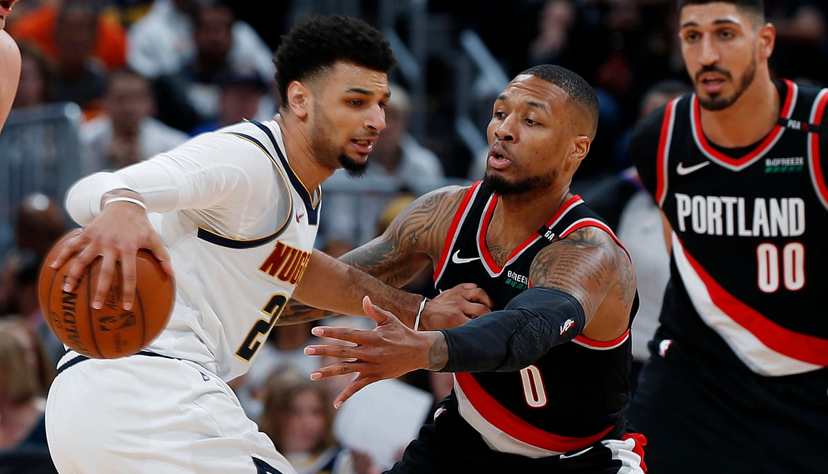Portland's Damian Lillard (center) and Enes Kanter look to defend Denver's Jamal Murray in Game 1 on April 29 (David Zalubowski)