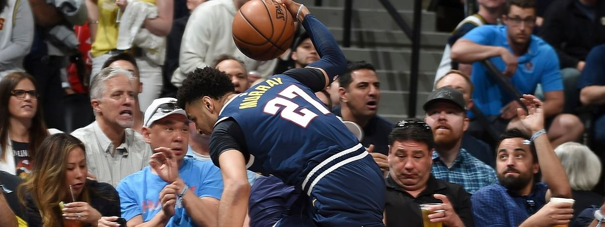 Nuggets guard Jamal Murray dives into the fans in the courtside seats to save a loose ball in the first half of Game 7 on May 12 (John Leyba)