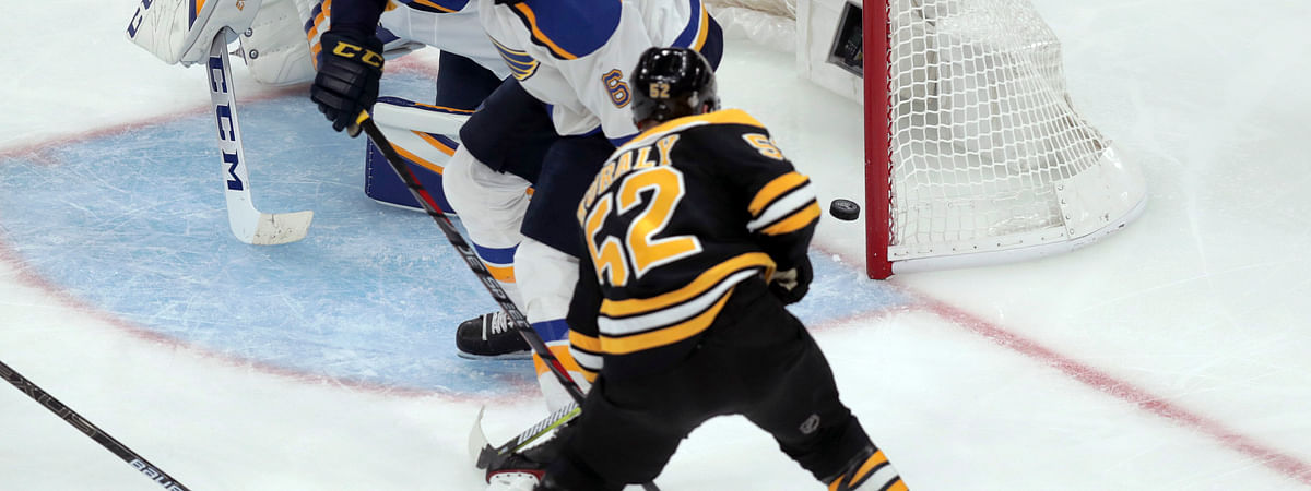 Boston Bruins' Sean Kuraly (52) scores a goal past St. Louis Blues goaltender Jordan Binnington (50) and Joel Edmundson (6) during the third period in Game 1 of the NHL hockey Stanley Cup Final, Monday, May 27, 2019, in Boston. (AP Photo/Charles Krupa)