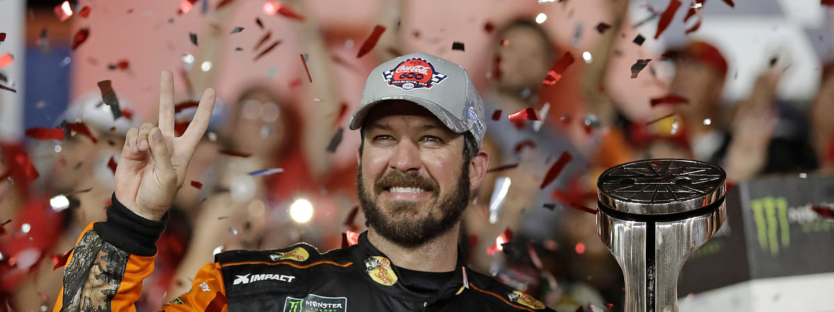Martin Truex Jr. poses with the trophy in Victory Lane after winning the Coca Cola 600 on May 26  (Chuck Burton)