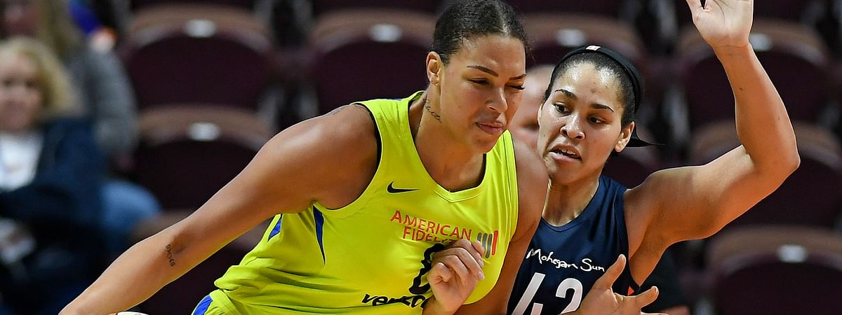 FILE - In this May 8, 2018, file photo, Dallas Wings' Liz Cambage, left, drives against Connecticut Sun's Brionna Jones during a preseason WNBA basketball game. Cambage has since been traded to the Las vegas Aces. (AP Photo/Jessica Hill, File)