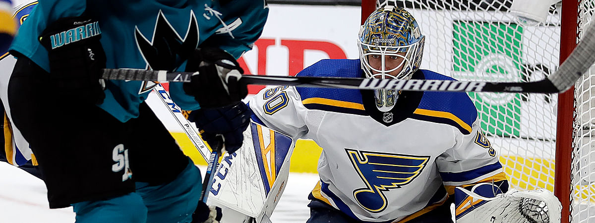 San Jose Sharks' Logan Couture, left, moves the puck against St. Louis Blues goalie Jordan Binnington during the first period in Game 2 of the NHL hockey Stanley Cup Western Conference finals on May 13, 2019.