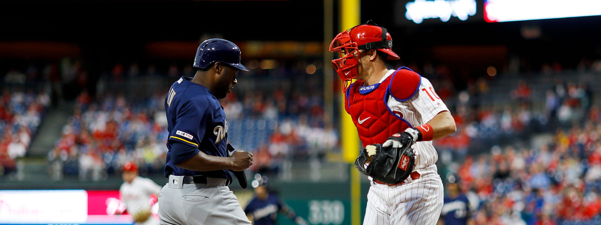 Brewers' Lorenzo Cain scores as he passes  Phillies catcher J.T. Realmuto in the first inning May 15  (Matt Slocum)