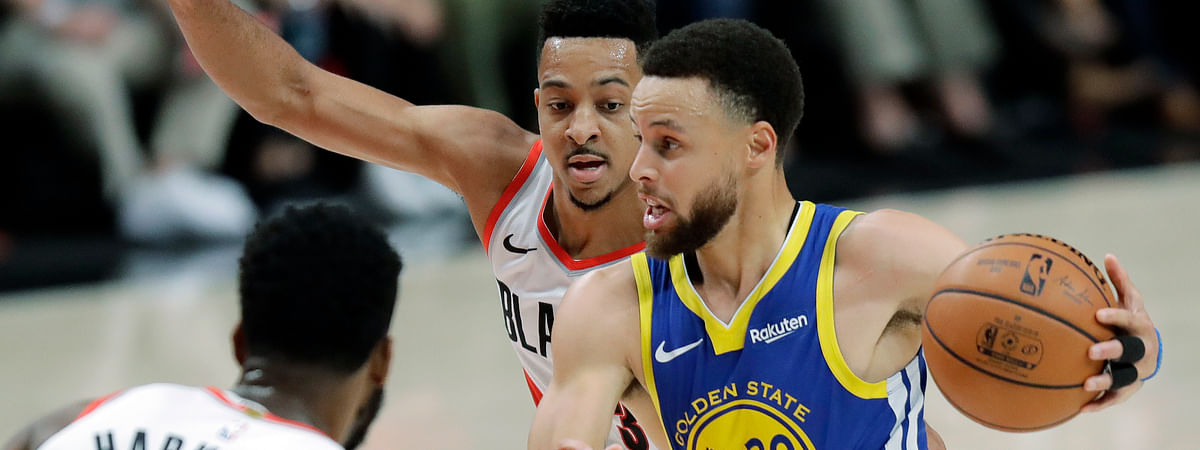 Golden State Warriors guard Stephen Curry drives past Portland Trail Blazers guard CJ McCollum, center, during the first half of Game 3 of the NBA basketball playoffs Western Conference finals on May 18, 2019.