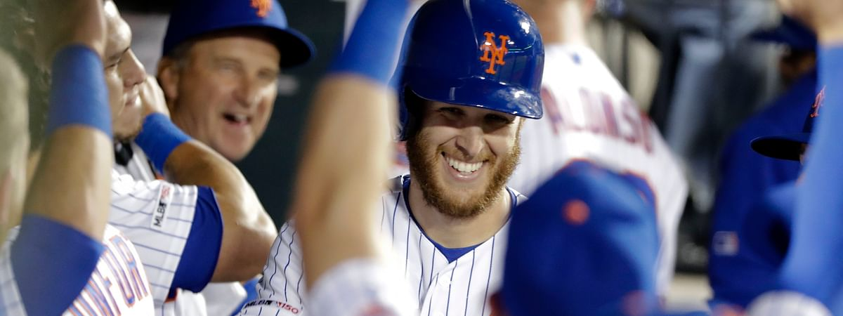In this April 2019 file photo, New York Mets starting pitcher Zack Wheeler smiles while celebrating with teammates after hitting a home run against the Philadelphia Phillies.