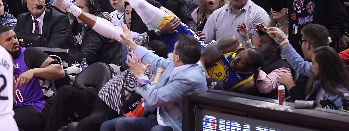 Golden State Warriors guard Andre Iguodala falls into the stands during the first half of Game 1 against the Toronto Raptors in basketball's NBA Finals, Thursday, May 30, 2019, in Toronto. (Frank Gunn/The Canadian Press via AP)