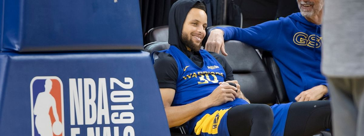 Warriors' Stephen Curry smiles as he sits beside the court at practice on June 12 (Frank Gunn/The Canadian Press)