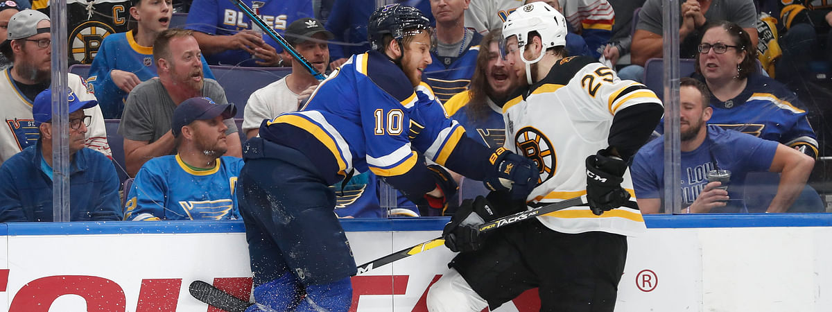 Blues center Brayden Schenn (10) and Bruins defenseman Brandon Carlo  battle along the board in Game 4 (Jeff Roberson)