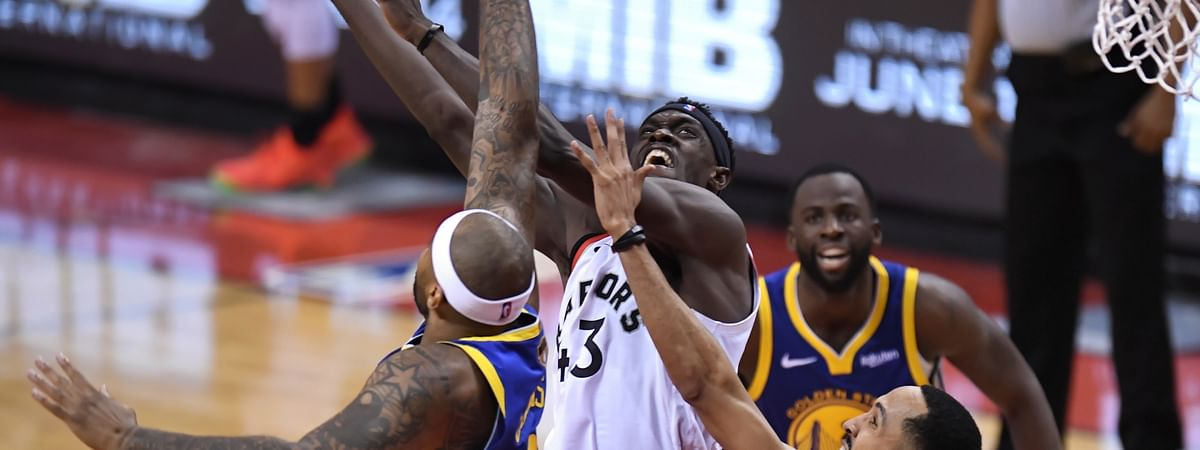 Toronto Raptors forward Pascal Siakam scores as Golden State Warriors center DeMarcus Cousins and guard Shaun Livingston, right, defend during the second half of Game 1 of basketball's NBA Finals on May 30, 2019.