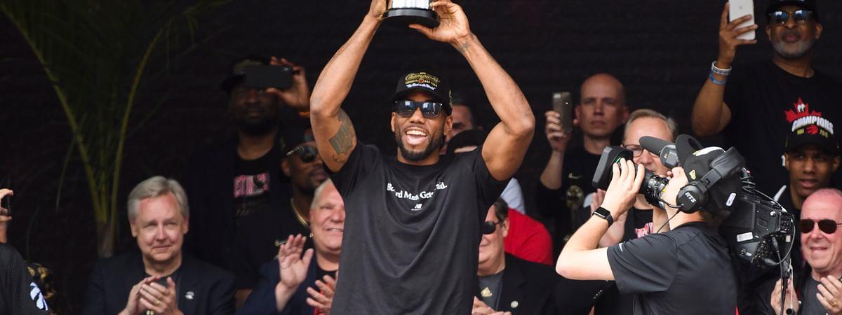Toronto Raptors forward Kawhi Leonard hoists the MVP trophy next to teammates during the team's NBA basketball championship parade in Toronto, Monday, June 17, 2019.