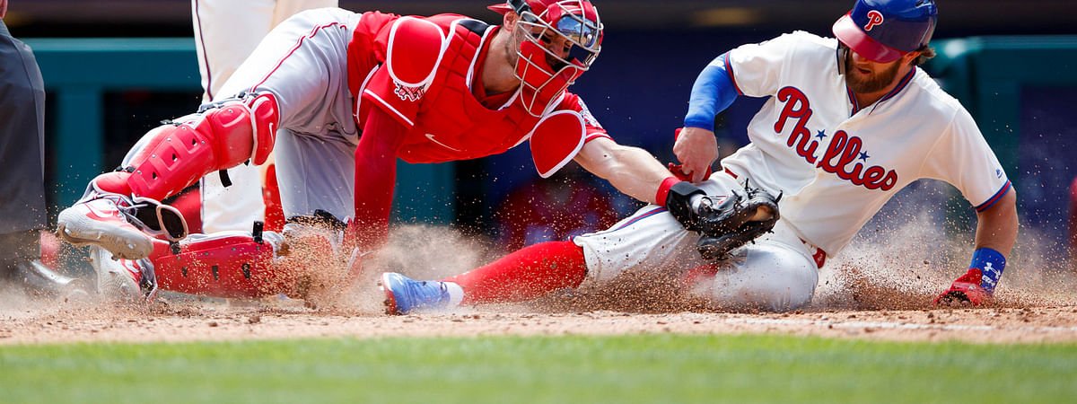 Phillies' Bryce Harper is tagged out by  Reds catcher Curt Casali after trying to steal home on  June 9 (Matt Slocum)