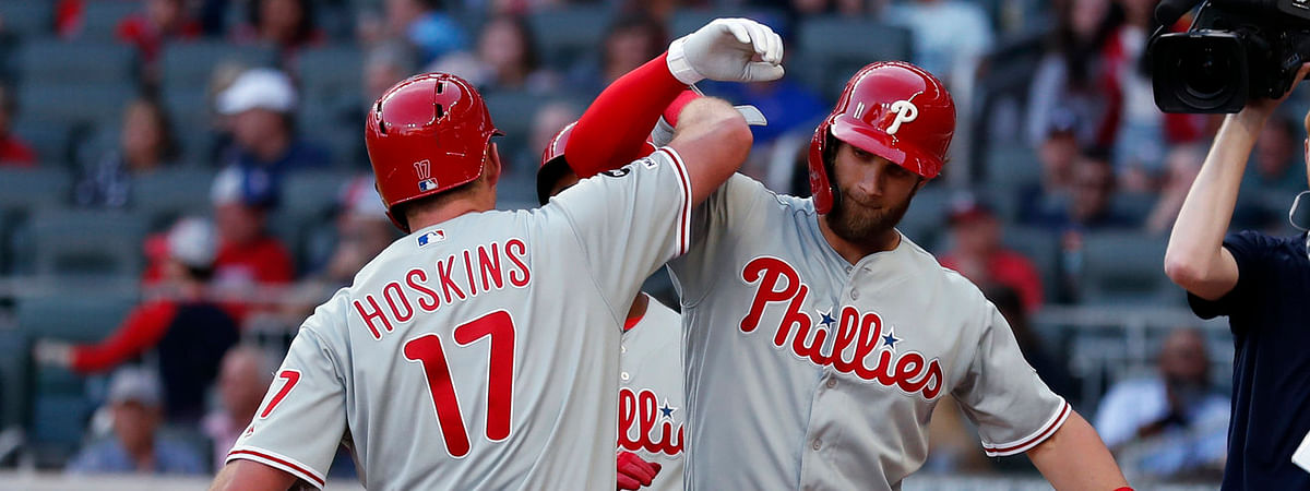 Phillies' Bryce Harper is greeted by Rhys Hoskins (17) after hitting a two-run home run in Atlanta on June 14. (AP Photo/John Bazemore)