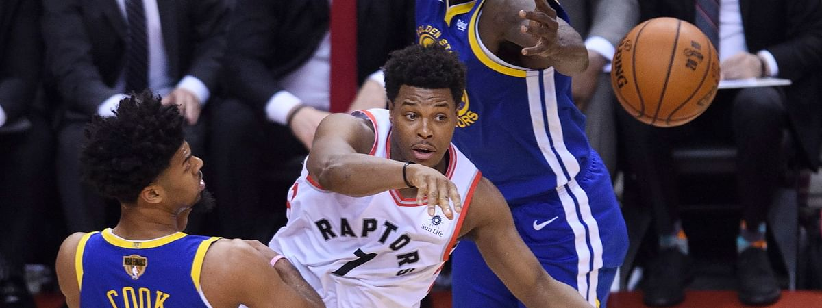 Raptors guard Kyle Lowry (7) passes while being defended by  Warriors Draymond Green (23) and  Quinn Cook in Game 1 on May 30 (Nathan Denette/The Canadian Press)