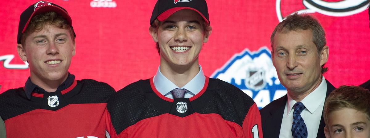 Jack Hughes, center, poses for photos after being selected by the New Jersey Devils with the first pick in the NHL hockey draft in Vancouver, British Columbia, Friday, June, 21, 2019. (Jonathan Hayward/The Canadian Press via AP)