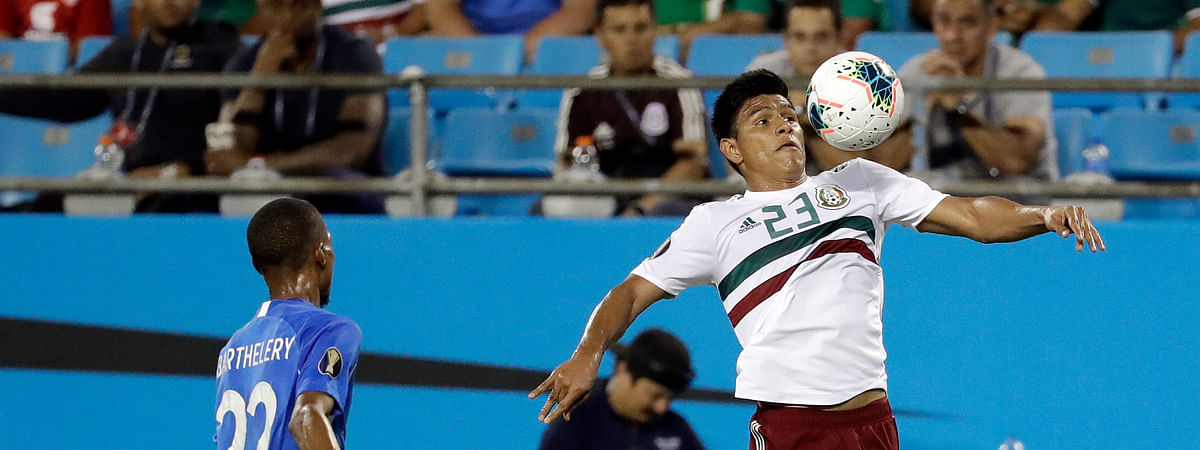 Mexico's Jesus Gallardo (23) moves the ball against Martinique's Romario Barthelery (22) during the first half of their CONCACAF Golf Cup soccer match in Charlotte, N.C., Sunday, June 23, 2019. (AP Photo/Chuck Burton)