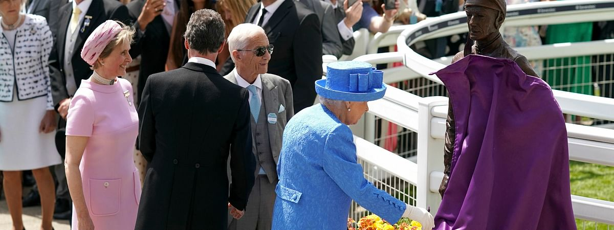 Britain's Queen Elizabeth II unveils a statue of famed jockey Lester Piggott, as Lester Piggott, front 3rd left, looks on with Sophie Countess of Wessex, left, during Derby Day at Epsom Racecourse, England, Saturday June 1, 2019. (John Walton/PA via AP)