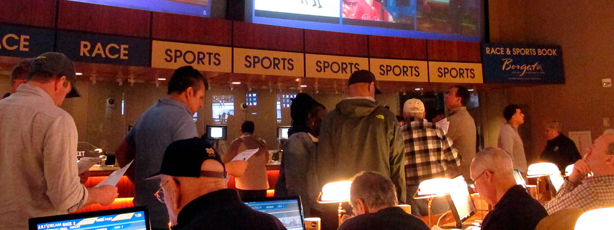 FILE - In this March 21, 2019, file photo, gamblers line up to place bets on the NCAA men's college basketball tournament at the Borgata casino in Atlantic City N.J.  (AP Photo/Wayne Parry, File)