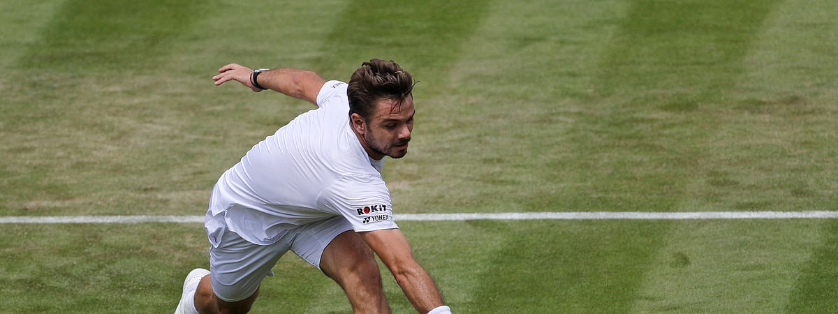 Switzerland's Stan Wawrinka returns in his Men's singles match against United States' Reilly Opelka during day three of the Wimbledon Tennis Championships in London, Wednesday, July 3, 2019. (AP Photo/Ben Curtis)