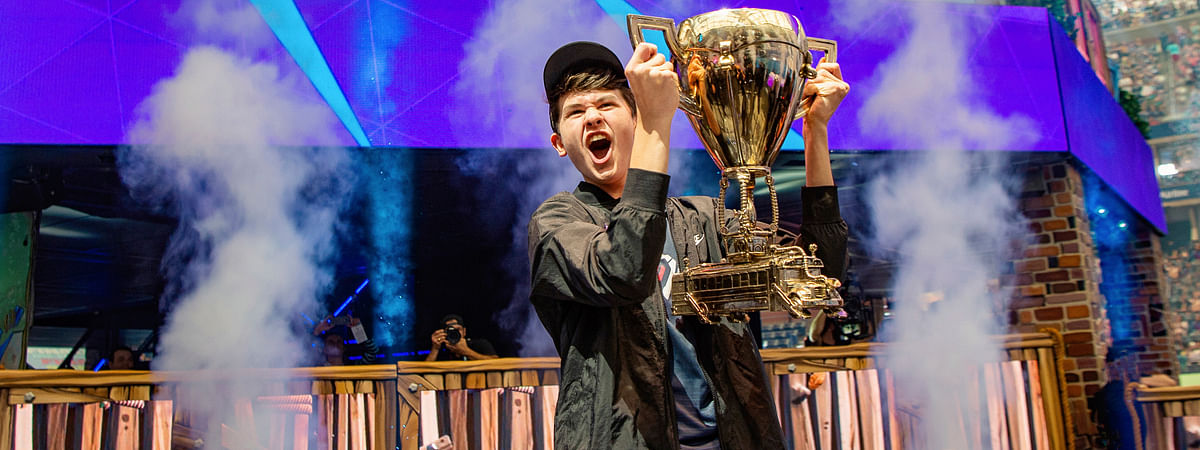 "In this July 28, 2019 photo, Kyle Giersdorf celebrates as he holds up the trophy after winning the Fortnite World Cup solo finals in New York. Giersdorf, of Pottsgrove, Pa. who goes by the name ""Bugha"" when competing, racked up the most points and won $3 million as the first Fortnite World Cup solo champion."