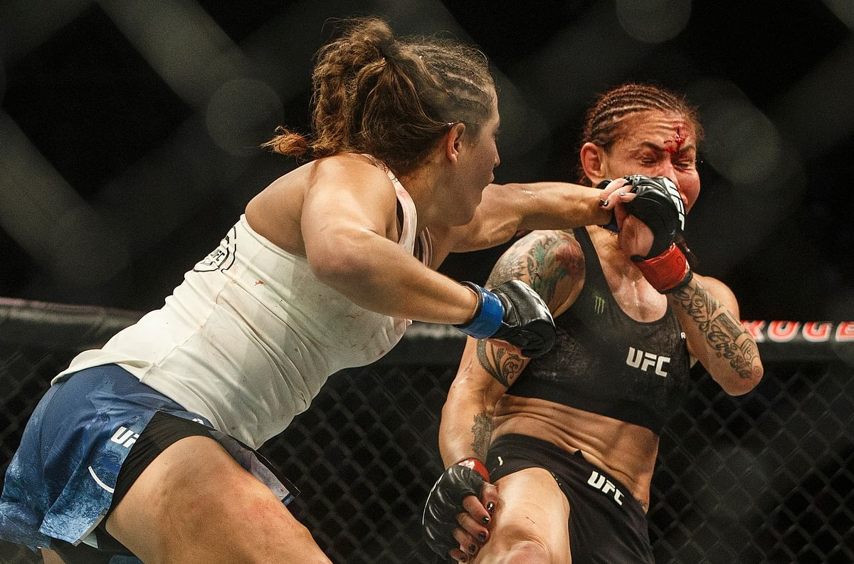 Cris Cyborg, right, is hit by Felicia Spencer during a mixed martial arts bout at UFC 240, in Edmonton, Alberta, Saturday, July 27, 2019. (Jason Franson/The Canadian Press via AP)
