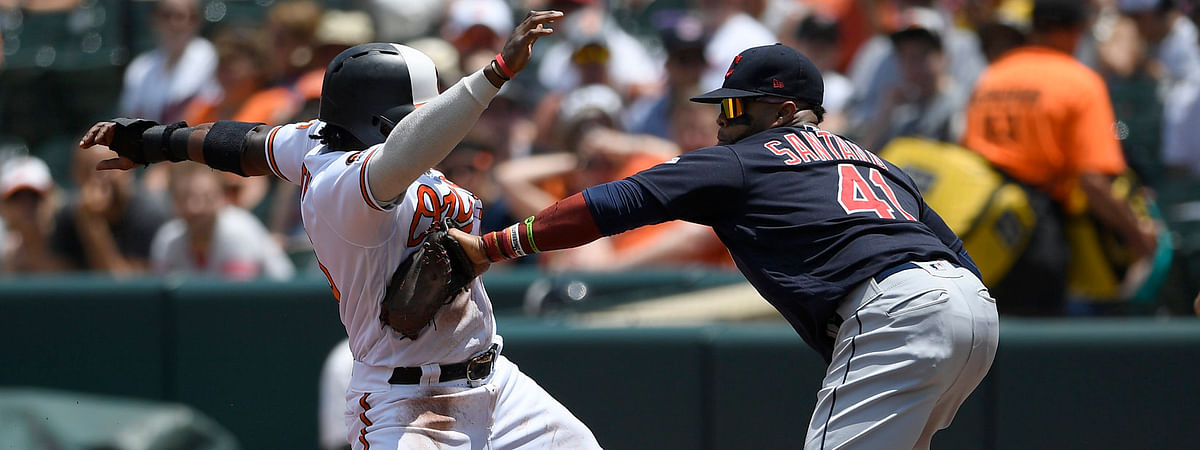 Orioles' Dwight Smith Jr. (left) is tagged out by  Indians first baseman Carlos Santana on a pickoff play during the first inning on June 30 (Nick Wass)