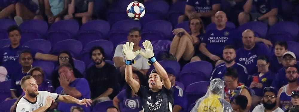Orlando City goalkeeper Brian Rowe (in black) leaps to stop a ball by the Union during their match on July 3 (Stephen M. Dowell/Orlando Sentinel)