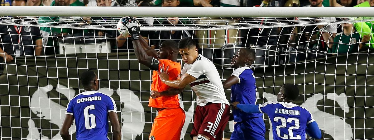 Haiti goalkeeper Jhony Placide, second from left, makes a save as he collides with Mexico defender Carlos Salcedo (3) as Haiti defender Jems Geffrard (6), Haiti defender Alex Christian (22) and Haiti defender Andrew Jean-Baptiste, second from right, look on during the first half of a CONCACAF Gold Cup soccer match Tuesday, July 2, 2019, in Glendale, Ariz. (AP Photo/Ross D. Franklin)