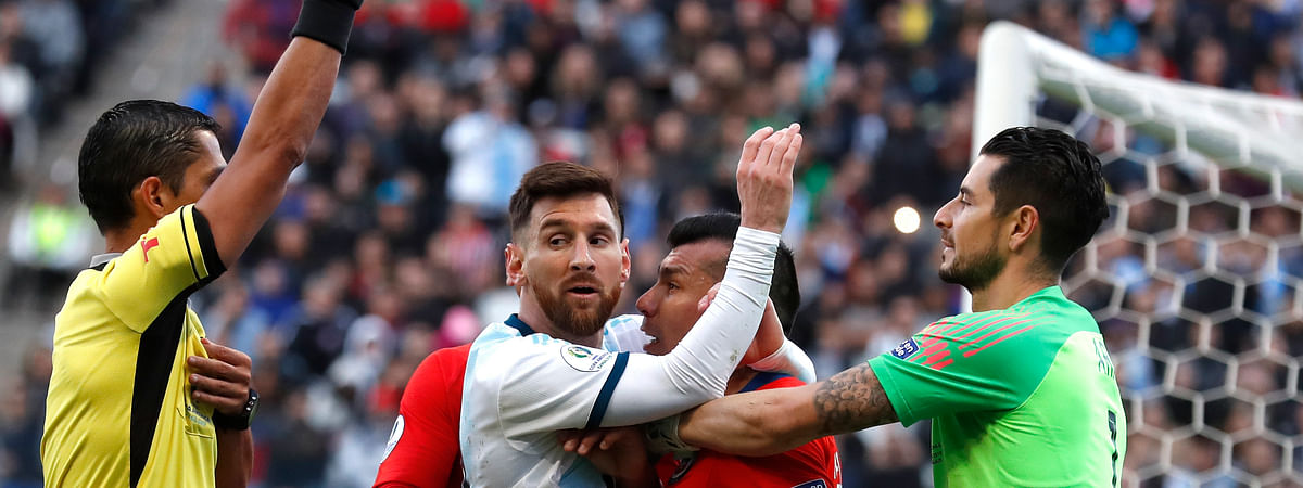 In this Saturday, July 6, 2019 photo, Argentina's Lionel Messi, center left, and Chile's Gary Medel, center right, scuffle as referee Mario Diaz, from Paraguay, left, shows the red card to both of them during Copa America third-place soccer match at the Arena Corinthians in Sao Paulo, Brazil. (AP Photo/Victor R. Caivano)