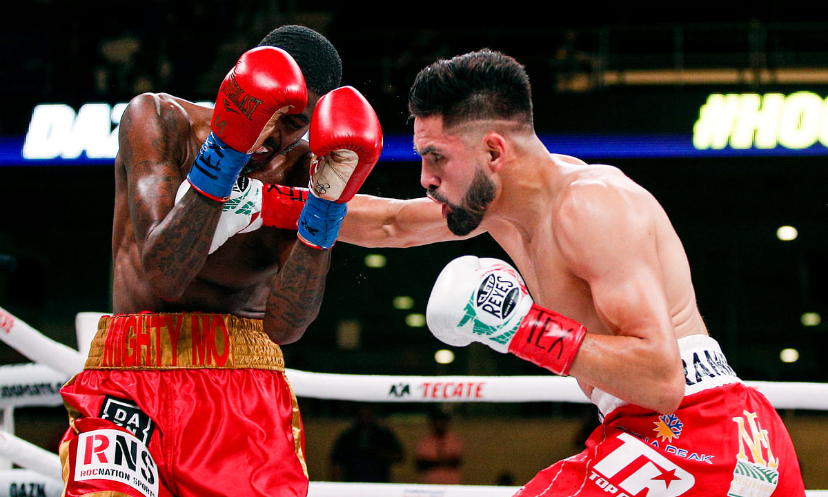 Jose Ramirez, right, lands a punch on Mauruce Hooker in the second round of a boxing match, Saturday, July 27, 2019, in Arlington, Texas. Ramirez won in the sixth round with a TKO. (AP Photo/Brandon Wade)