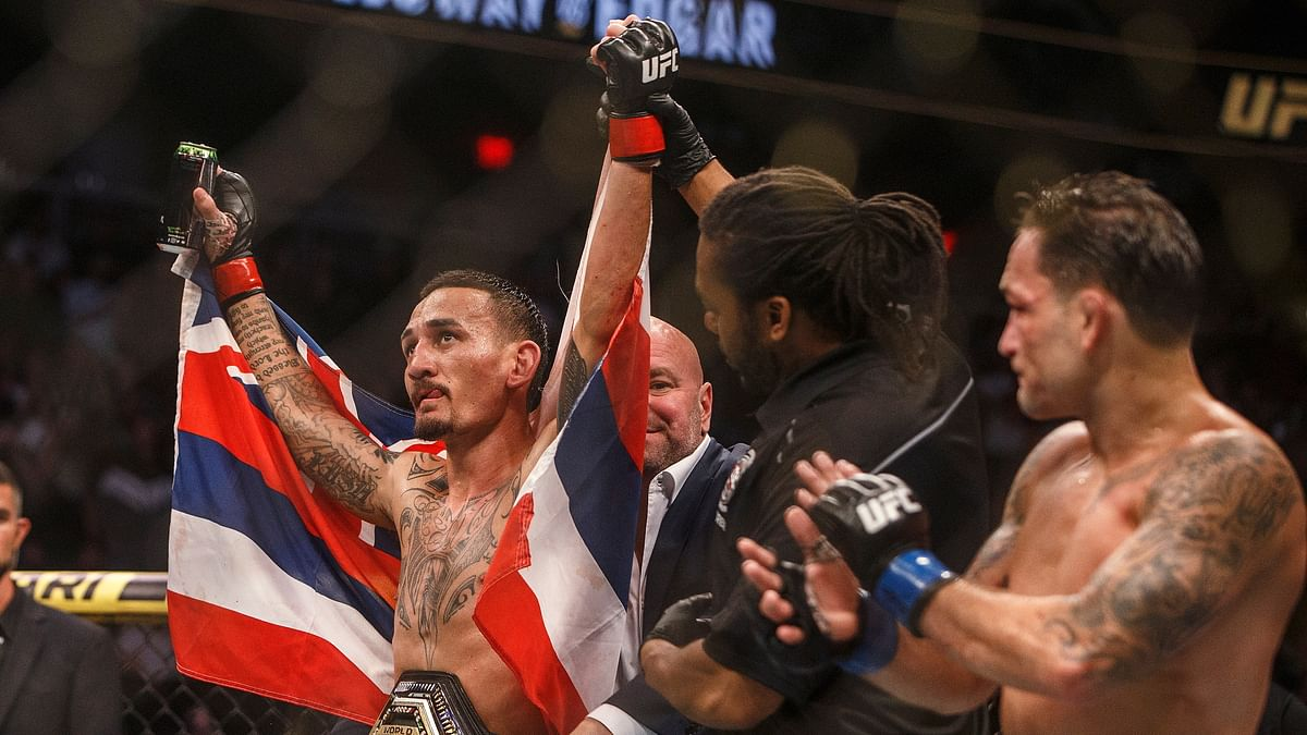 Max Holloway celebrates the win over Frankie Edgar during a mixed martial arts bout at UFC 240, in Edmonton, Alberta, Saturday, July 27, 2019. (Jason Franson/The Canadian Press via AP)