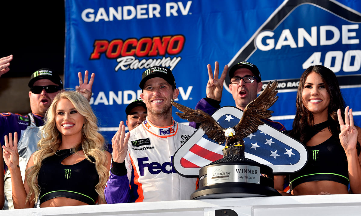 Denny Hamlin celebrates in victory lane after winning a NASCAR Cup Series auto race, Sunday, July 28, 2019, in Long Pond, Pa. (AP Photo/Derik Hamilton)