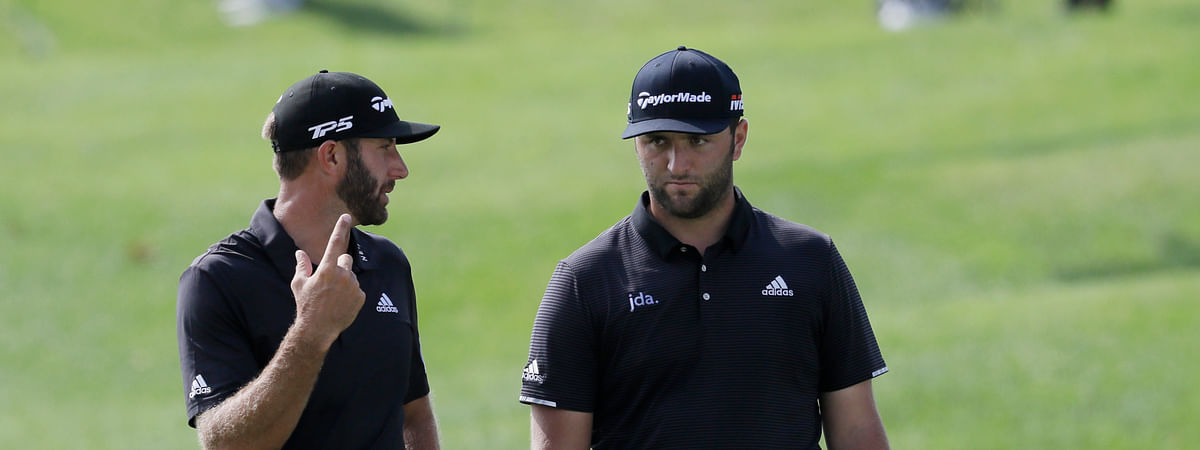 Dustin Johnson, left, and Jon Rahm, of Spain, talk during the first round of the Northern Trust golf tournament at Liberty National Golf Course, Thursday, Aug. 8, 2019 in Jersey City, N.J. Johnson finished the first round one shot off the lead. (AP Photo/Mark Lennihan)