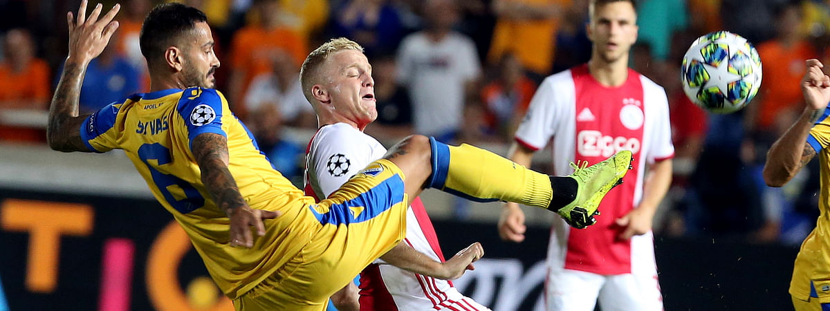 Ajax's Donny van de Beek, right, challenges for the ball with APOEL's Savvas Gentsoglou during the Champions League qualifying play-off first leg soccer match between APOEL Nicosia and AFC Ajax at GSP stadium in Nicosia, Cyprus on Aug. 20, 2019.