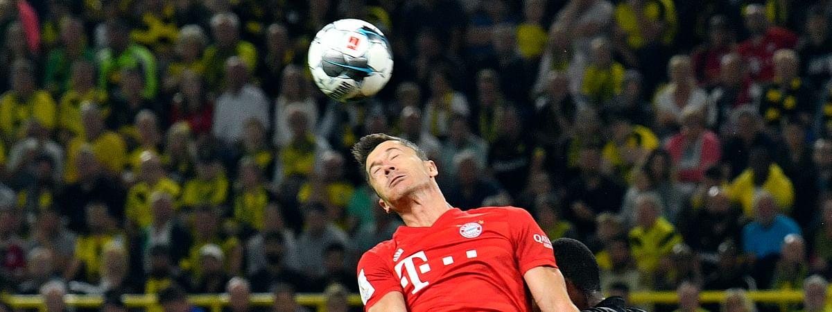 Bayern's Robert Lewandowski, center, jumps for the ball with Dortmund's Omer Toprak, left, and Dortmund's Manuel Akanji during the German Supercup final soccer match between Borussia Dortmund and Bayern Munich in Dortmund, Germany, Saturday, Aug. 3, 2019. (AP Photo/Martin Meissner)