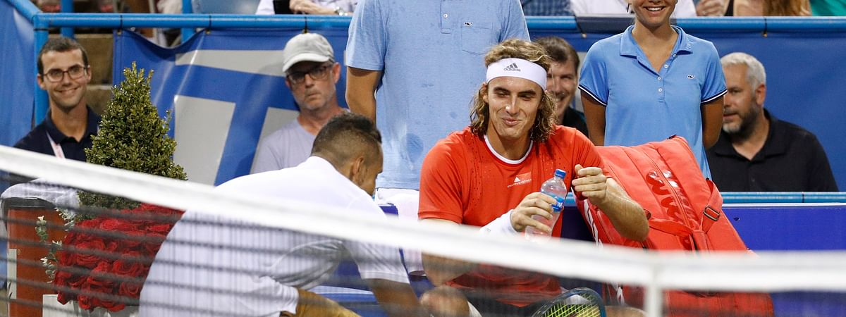 Nick Kyrgios, left, of Australia, delivers a pair of shoes to Stefanos Tsitsipas, of Greece, during a break in play in a semifinal at the Citi Open tennis tournament, Saturday, Aug. 3, 2019, in Washington.