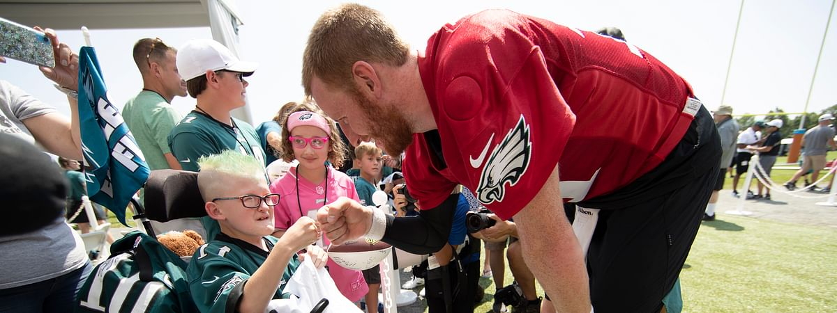 Philadelphia Eagles quarterback Carson Wentz bumps fists with eleven-year-old Giovanni Hamilton who is attending the practice as part of a wish granted by Bianca's Kids at the NFL football team's training camp in Philadelphia, Friday, July 26, 2019.