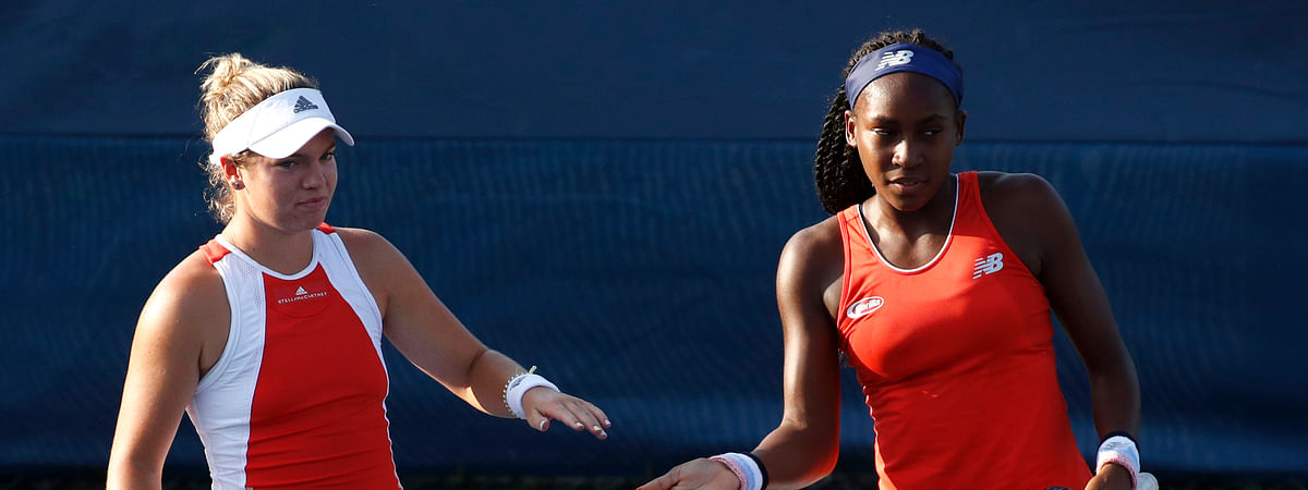Caty McNally, left, slaps hands with Cori Gauff as they play the women's doubles final against Fanny Stollar, of Hungary, and Maria Sanchez at the Citi Open tennis tournament, Saturday, Aug. 3, 2019, in Washington.