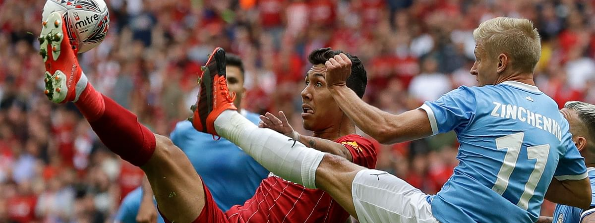 Liverpool's Roberto Firmino challenges for the ball with Manchester City's Oleksandr Zinchenko during the English Community Shield soccer match between Liverpool and Manchester City at Wembley stadium in London on Aug. 4, 2019.