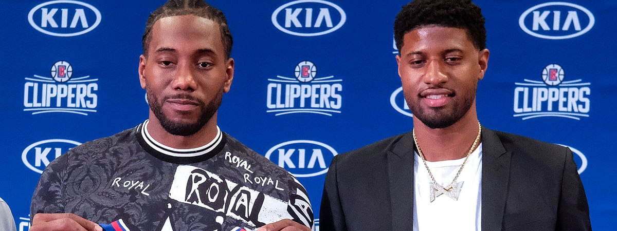 Kawhi Leonard, left, and Paul George pose with their new team jerseys during a press conference in Los Angeles on July 24, 2019.