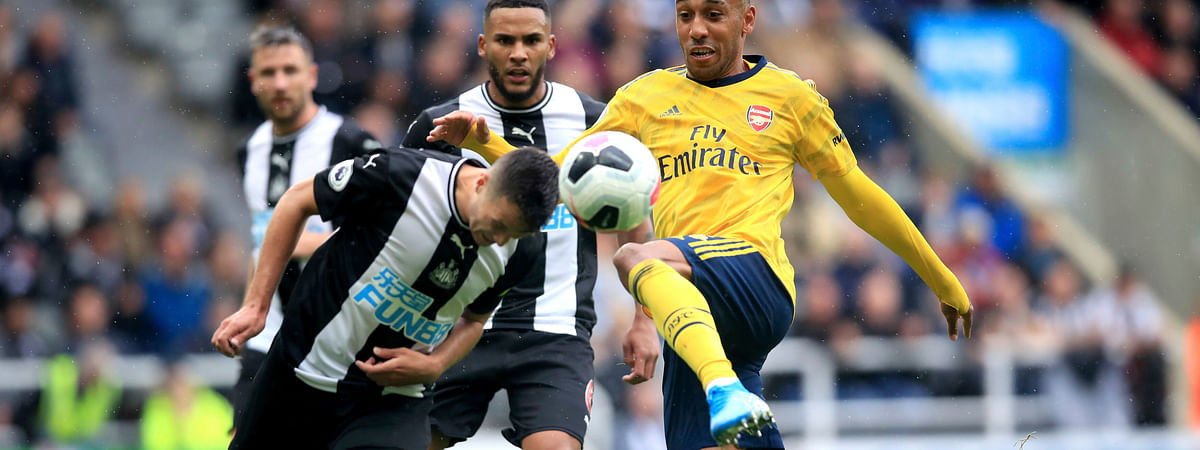 Arsenal's Pierre-Emerick Aubameyang, right, and Newcastle United's Javier Manquillo battle for the ball during the English Premier League soccer match between Newcastle United and Arsenal, at St James' Park, in Newcastle, England, Sunday, Aug. 11, 2019.