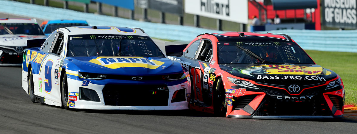 Chase Elliott (9) holds off an attempt to pass by Martin Truex, Jr., after a restart following a yellow caution flag during a NASCAR Cup series auto race at Watkins Glen International, Sunday, Aug. 4, 2019, in Watkins Glen, N.Y.  (AP Photo/John Munson)