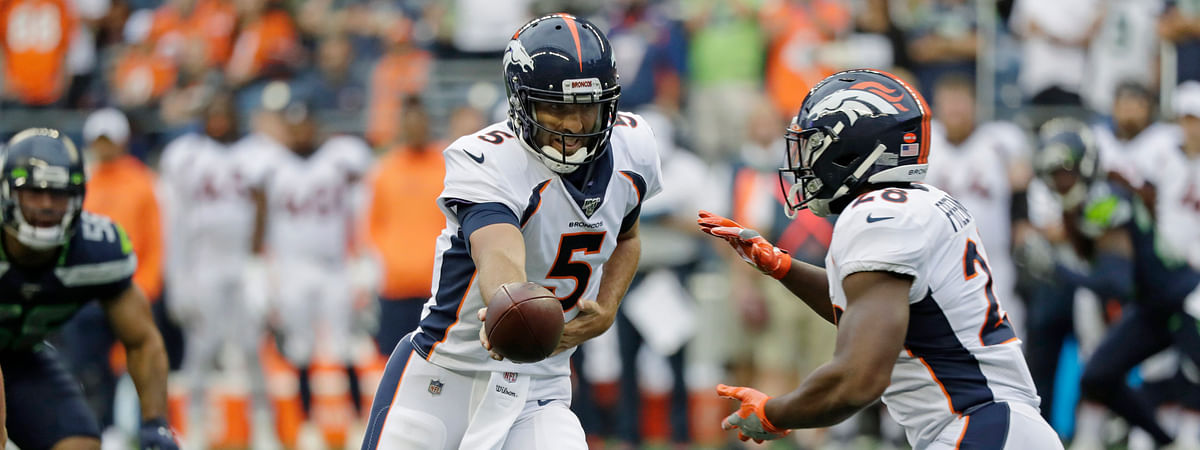 In this Aug. 8, 2019 photo, Denver Broncos quarterback Joe Flacco hands off to running back Royce Freeman during the first half of the team's NFL football preseason game against the Seattle Seahawks in Seattle.