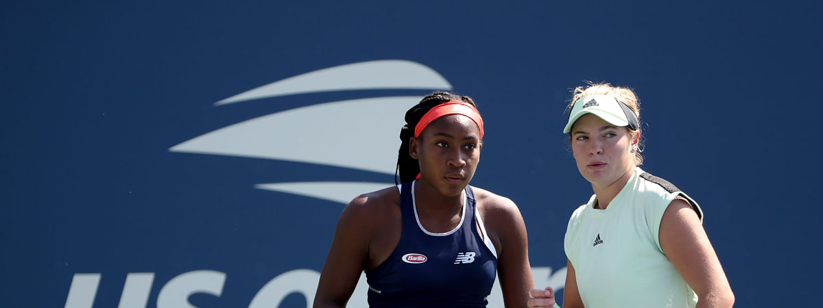 Coco Gauff, left, and Catherine McNally, both of the United States, talk during a first round doubles match against Julia Goerges, of Germany, and Katerina Siniakova, of the Czech Republic, at the US Open tennis championships Friday, Aug. 30, 2019, in New York. (AP Photo/Kevin Hagen)
